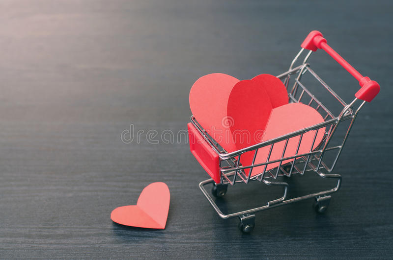 Full of hearts in the shopping cart on wooden floor. Valentines concept, Full of hearts in the shopping cart on wooden floor royalty free stock photography