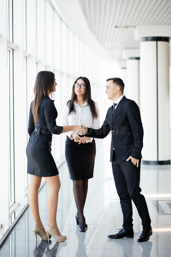 Full height Businessman And businesswoman shaking hands In bright Office royalty free stock photos