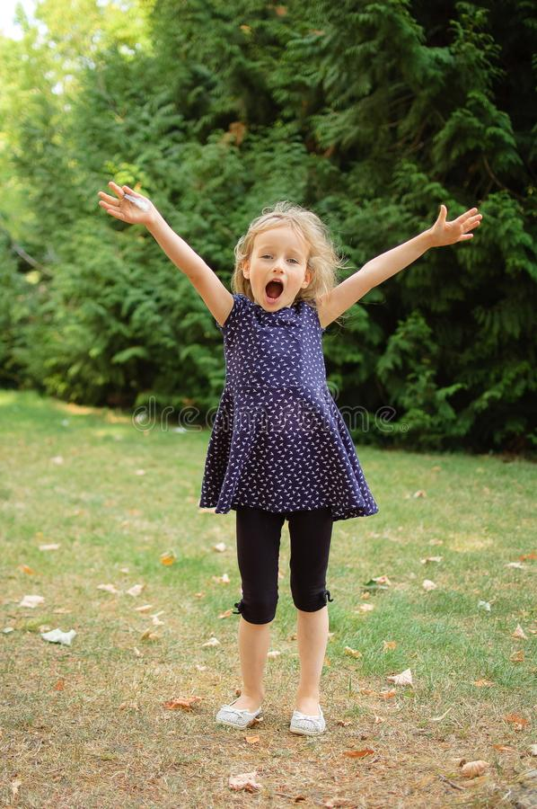 Full Height Outdoors Portrait of Happy Acive Blonde Girl Screaming in the Park During Summer Day stock photography