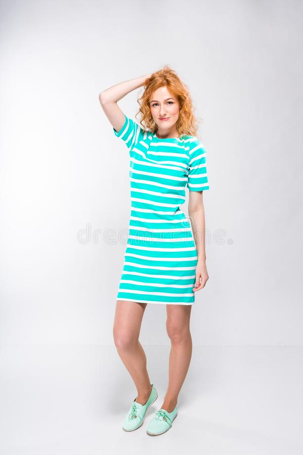 Full-height portrait of a young, beautiful woman with red curly hair in a summer dress with strips of blue in the studio on a gray stock images