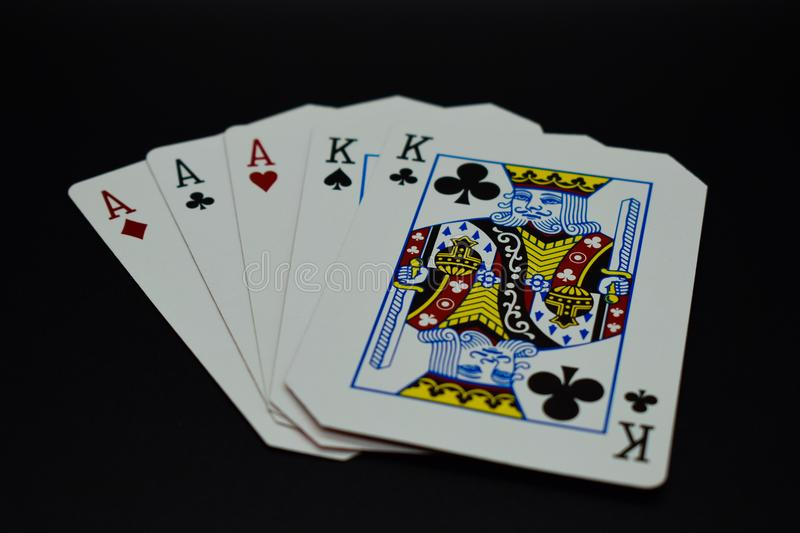Full house aces full of kings of cards in poker game against black background. Aces gamble gambling las vegas style club heart king bet aces full of kings deck stock photography