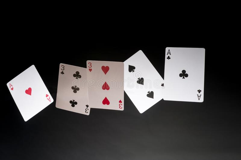 Full House. Flying playing cards on a dark background - Full House royalty free stock images
