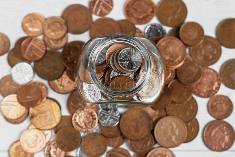 Full jar of coins from above, surrounded by loose change. Money saving and investment concept.  royalty free stock image