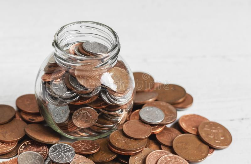 Full jar of coins on a table, surrounded by loose change. Money savings concept with copy space.  stock photography