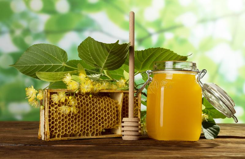 Full jar of May honey, bee honeycombs and sprig of Linden, spoon on table. Full jar of May honey, bee honeycombs and sprig of Linden, wooden spoon on table stock photography