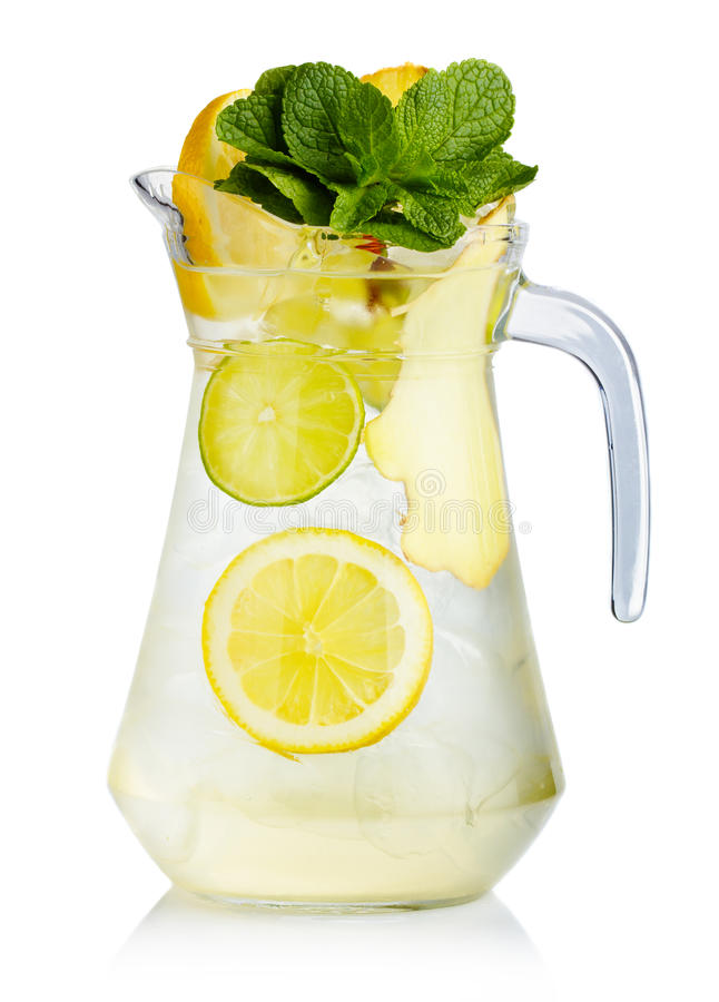 Full jug of fresh birch juice with lemon, ginger and mint leaves royalty free stock image