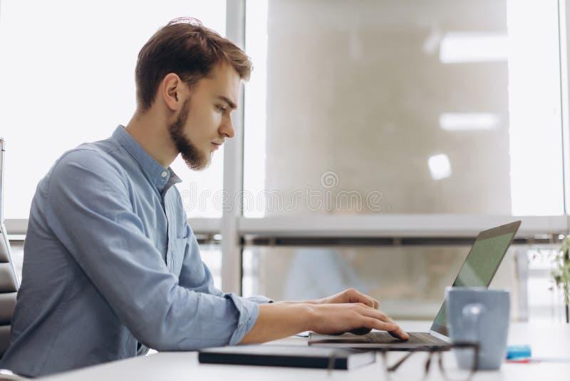 Full koncentration på arbete Stilig ung skäggman i skjortaarbete på bärbara datorn, medan sitta på hans arbetsplats royaltyfria foton