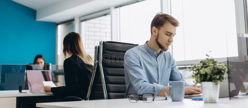 Full koncentration på arbete Stilig ung skäggman i skjortaarbete på bärbara datorn, medan sitta på hans arbetsplats arkivfoton