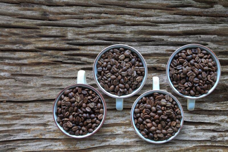 Full kopp av högkaffebönan på den åldriga lantliga trätabellen med kopieringsutrymme från bästa sikt royaltyfri fotografi