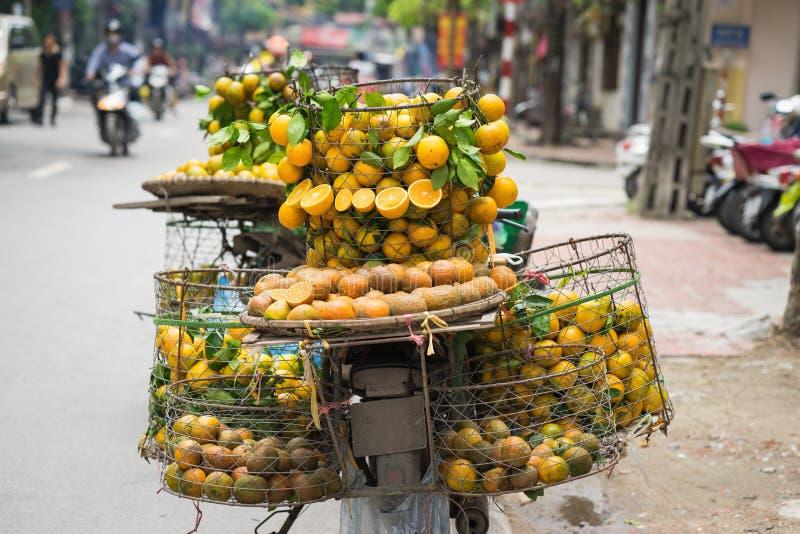 Full korg av orange frukt på försäljarecykeln på den Hanoi gatan, Vietnam royaltyfria foton