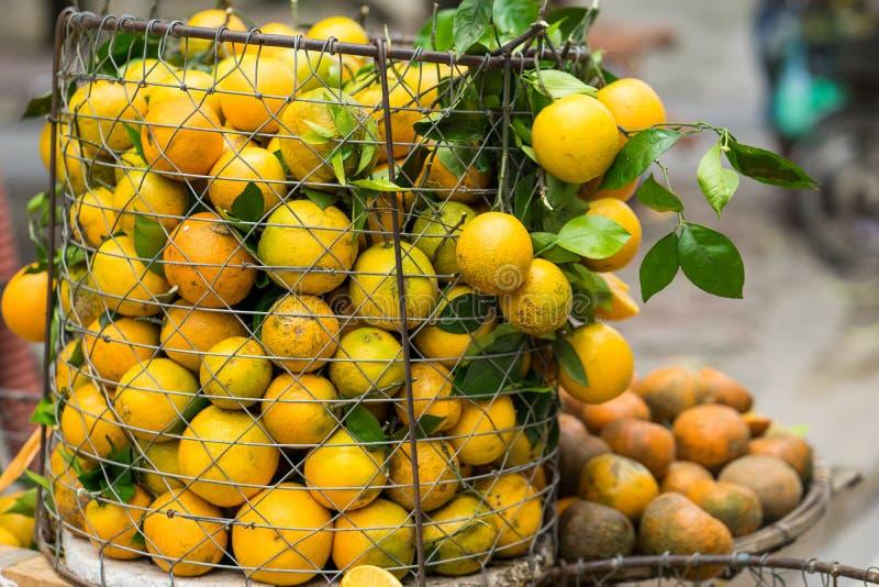 Full korg av orange frukt på försäljarecykeln på den Hanoi gatan, Vietnam arkivfoto