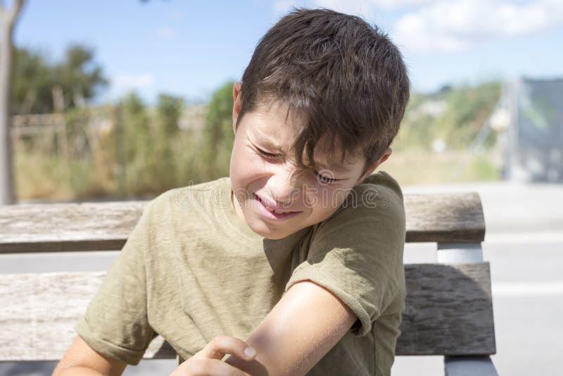 Full kropp av det asiatiska barnet som såras på armbågen Ledsen pojke som är stönande med arkivbilder