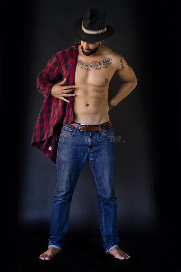 Full kropp av en ung man som sätter på hans skjorta, i jeans arkivfoton