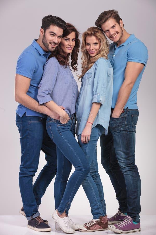 Full kroppbild av fyra lyckliga tillfälliga personer som tillsammans står royaltyfri fotografi