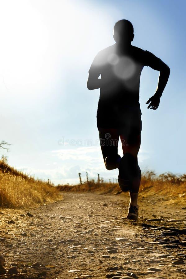 Full kroppkontur av extrem manspring för argt land på det lantliga spåret som joggar på solnedgången royaltyfria foton