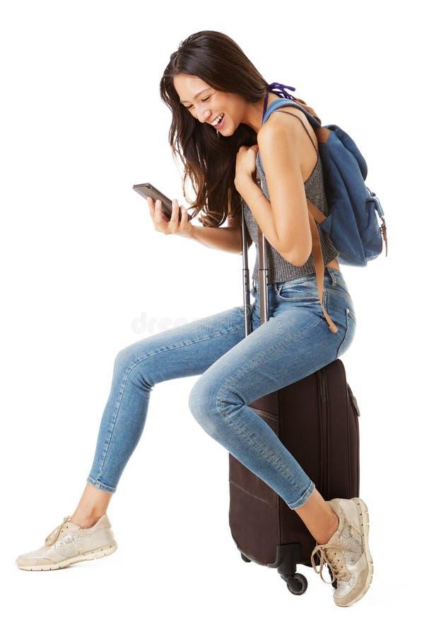 Full kroppsida av den lyckliga asiatiska kvinnliga handelsresanden som sitter på resväskan och ser mobiltelefonen mot isolerad vi royaltyfri bild