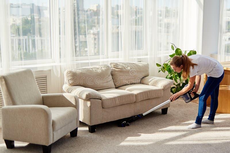 Full kroppstående av den unga kvinnan i den vita skjortan och jeans som gör ren matta med dammsugare i vardagsrum, kopieringsutry royaltyfria foton