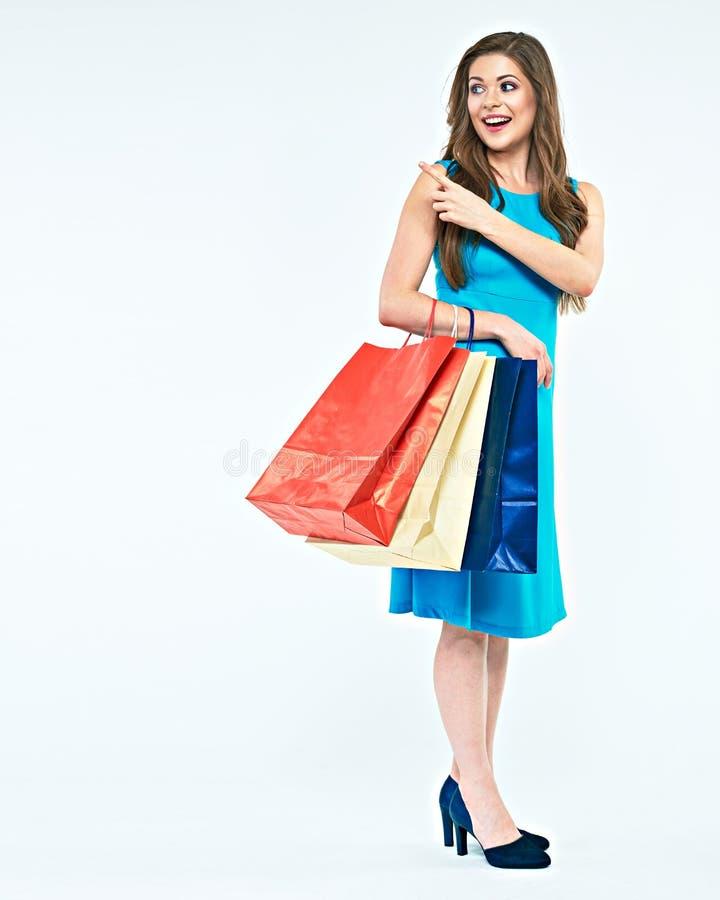 Full kroppstående av den unga kvinnan med shoppingpåsen som pekar fena royaltyfri fotografi