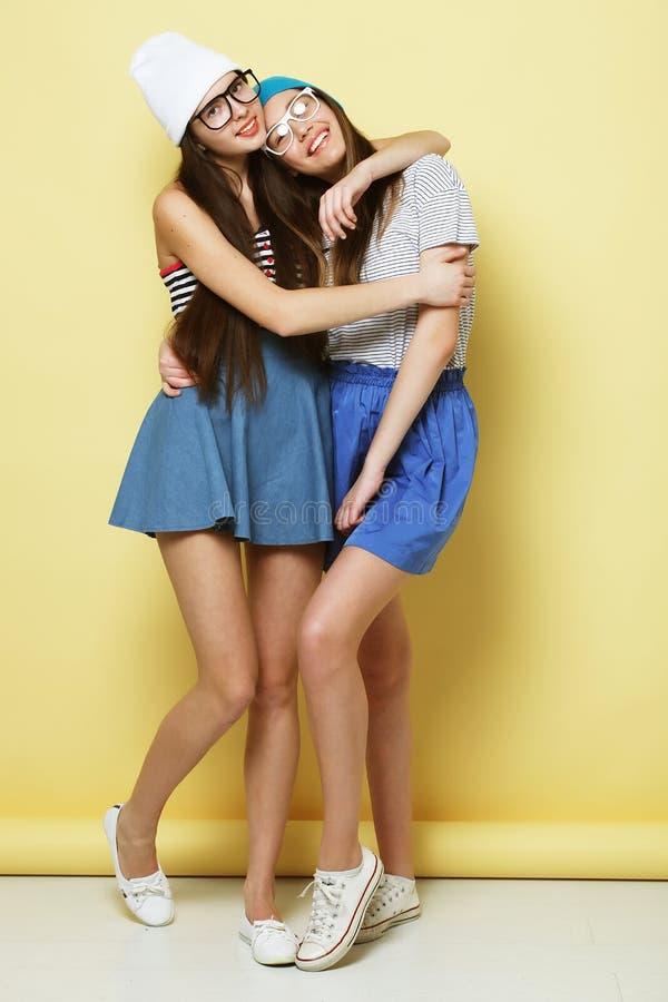 Full kroppstående av två hipsterflickor över gul bakgrund fotografering för bildbyråer