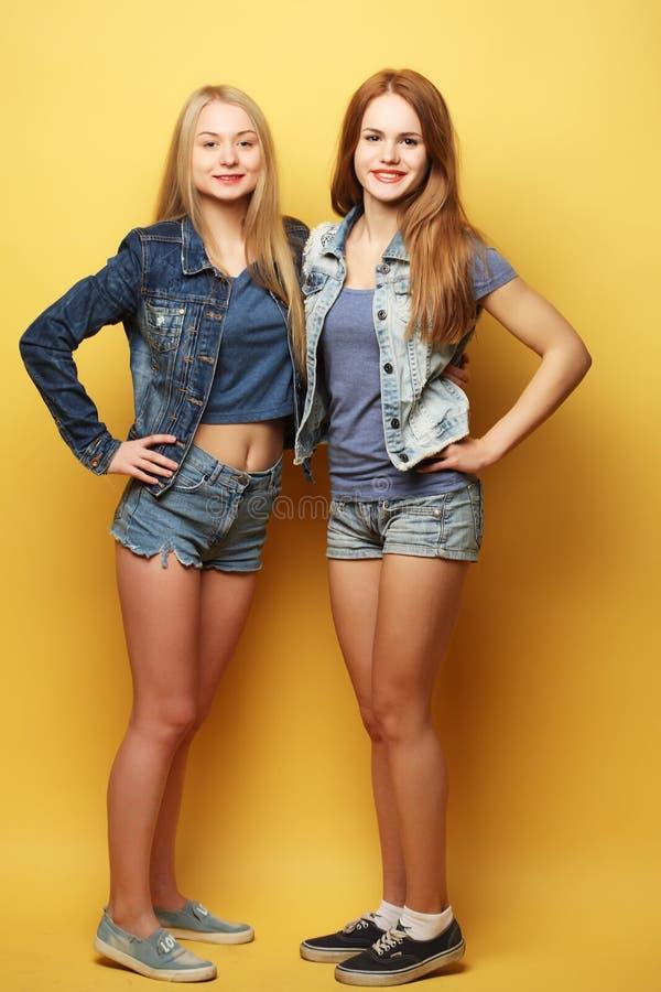 Full kroppstående av två hipsterflickor över gul bakgrund arkivbilder