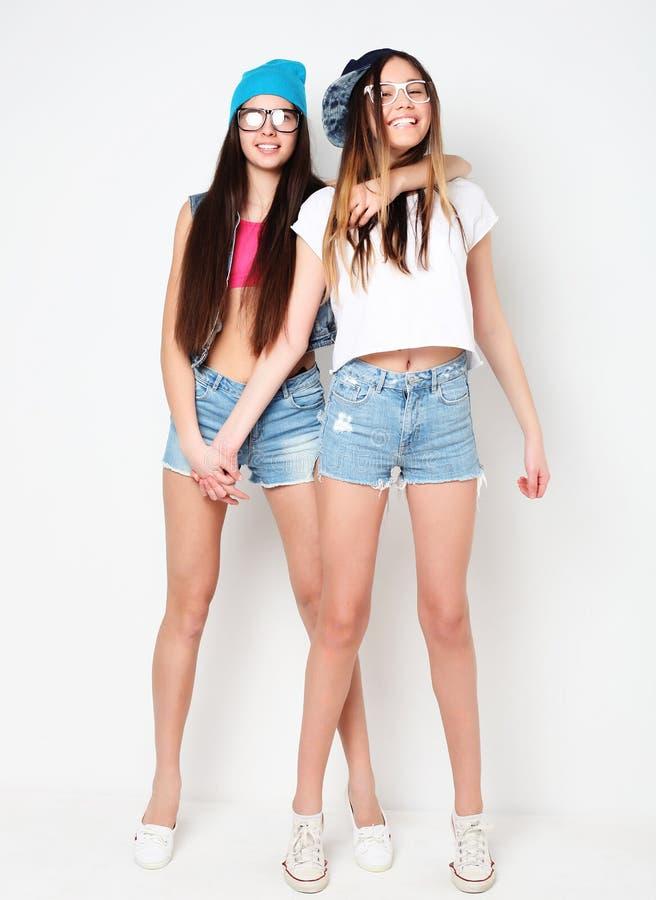 Full kroppstående av två hipsterflickor över vit bakgrund arkivfoto