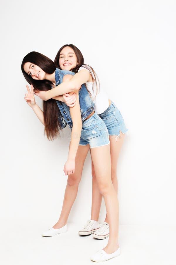 Full kroppstående av två hipsterflickor över vit bakgrund arkivfoton