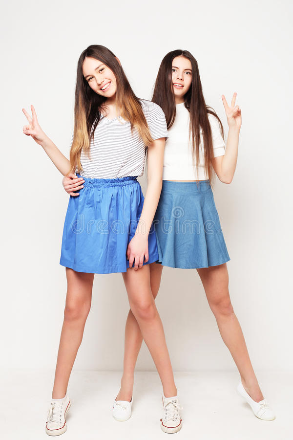 Full kroppstående av två lyckliga flickor över vit bakgrund royaltyfri fotografi