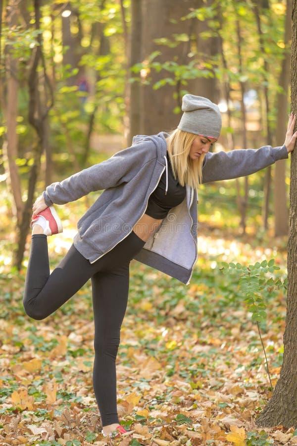Full kroppstående för sida av en sportig ung kvinna som gör sträckning fotografering för bildbyråer