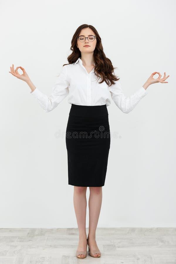 Full kvinna för längdståendeaffär som gör avslappnande yoga för ställning som isoleras på vanlig vit bakgrund royaltyfria foton