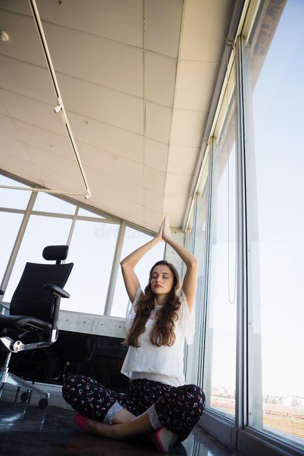 Full längd av affärskvinnan som gör yoga arkivfoto