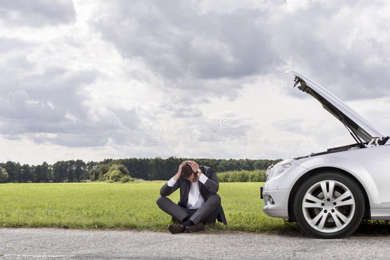 Full längd av affärsmannen med händer på head sammanträde med den brutna ner bilen på bygd arkivfoton