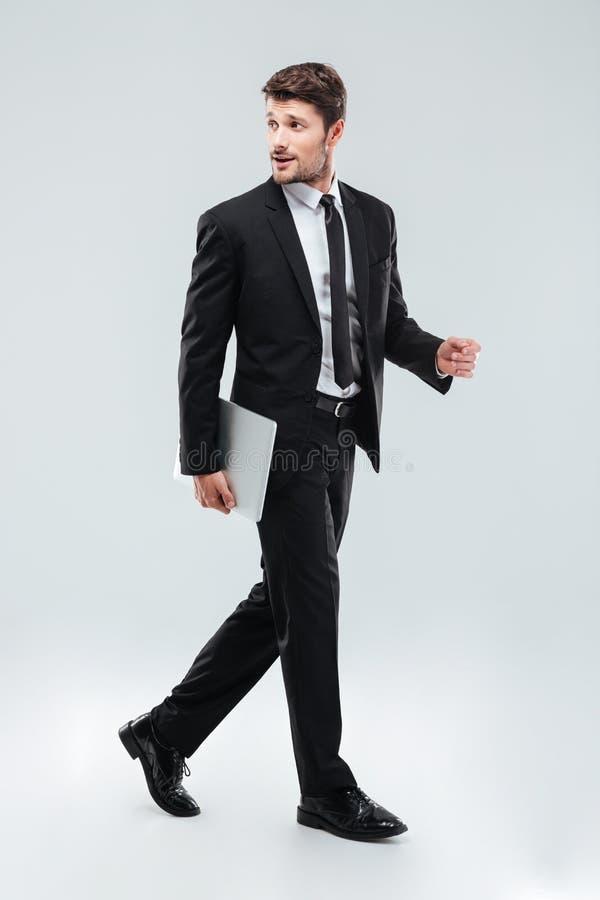 Full längd av den attraktiva unga affärsmannen som går och rymmer bärbara datorn fotografering för bildbyråer