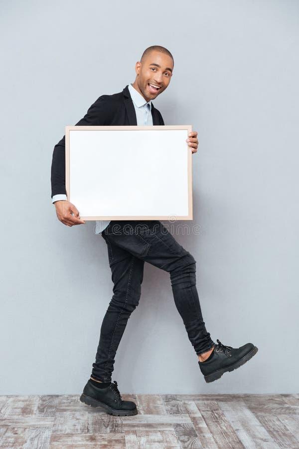 Full längd av den gladlynta afrikanska mannen som går och rymmer whiteboard fotografering för bildbyråer