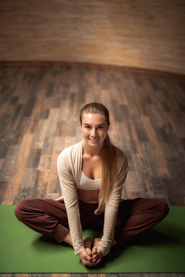 Full längd av den gladlynta damen som sitter på den matta yogan och ser lycklig arkivfoto