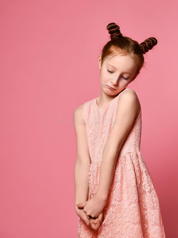 Full längd av den härliga lilla flickan i klänningen som står och poserar över rosa bakgrund arkivfoto