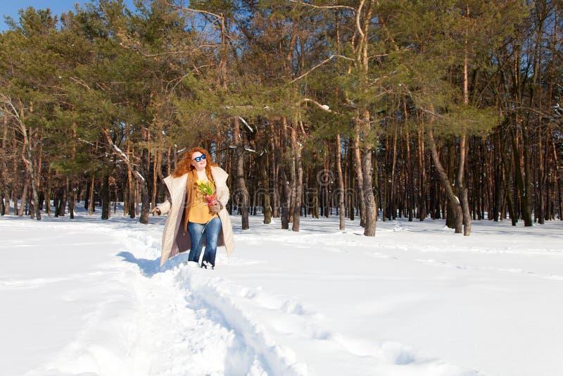 Full längd av den lyckliga nätta kvinnan som går till och med snöig skog royaltyfria foton
