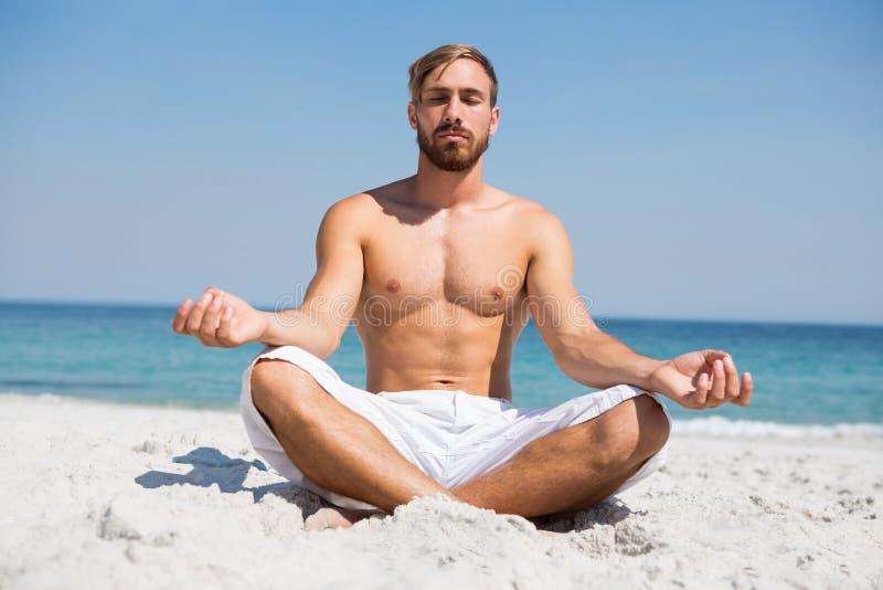 Full längd av den shirtless mannen som mediterar på stranden arkivbild