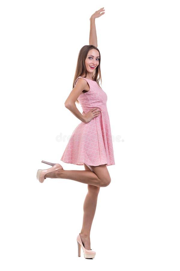 Full längd av den sinnliga kvinnan i kort klänningdans mot isolerad vit arkivfoton
