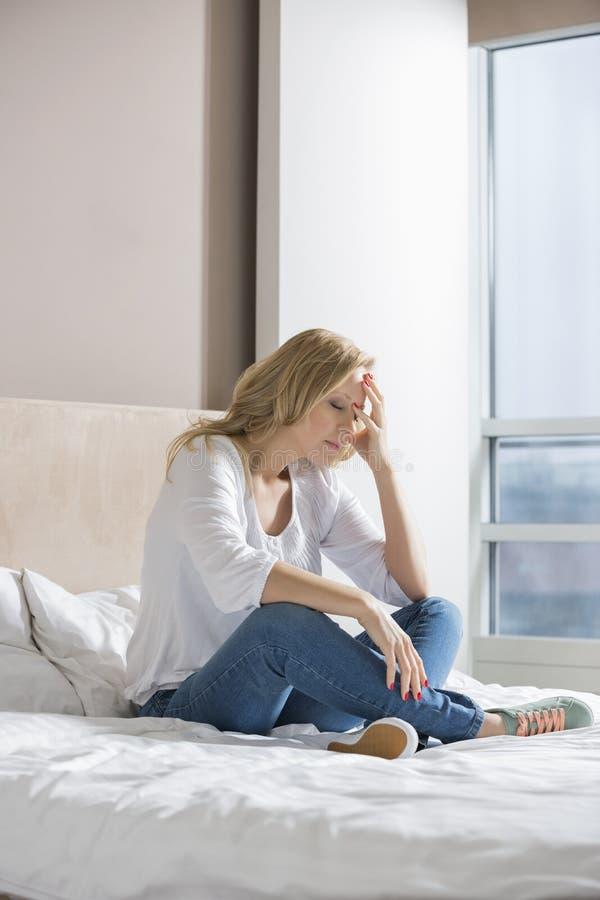 Full längd av den stressade kvinnan med handen på framsidasammanträde på säng royaltyfria bilder