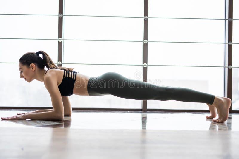Full längd av den unga härliga kvinnan i sportswearen som gör plankan, medan stå framme av fönster på idrottshallen royaltyfria foton