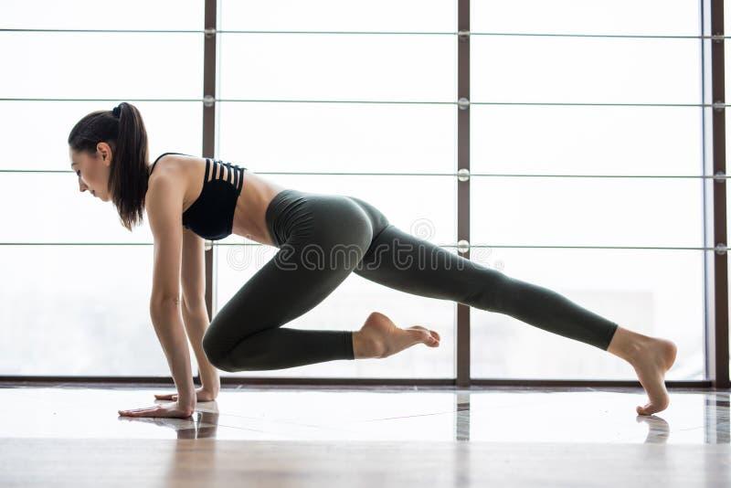 Full längd av den unga härliga kvinnan i sportswearen som gör plankan, medan stå framme av fönster på idrottshallen fotografering för bildbyråer