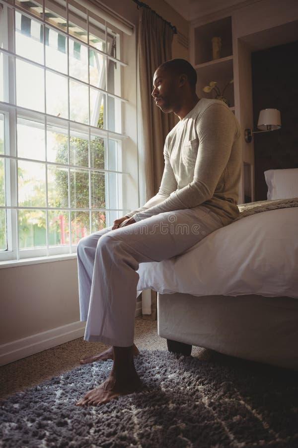Full längd av fundersamt mansammanträde på säng vid fönstret royaltyfri fotografi