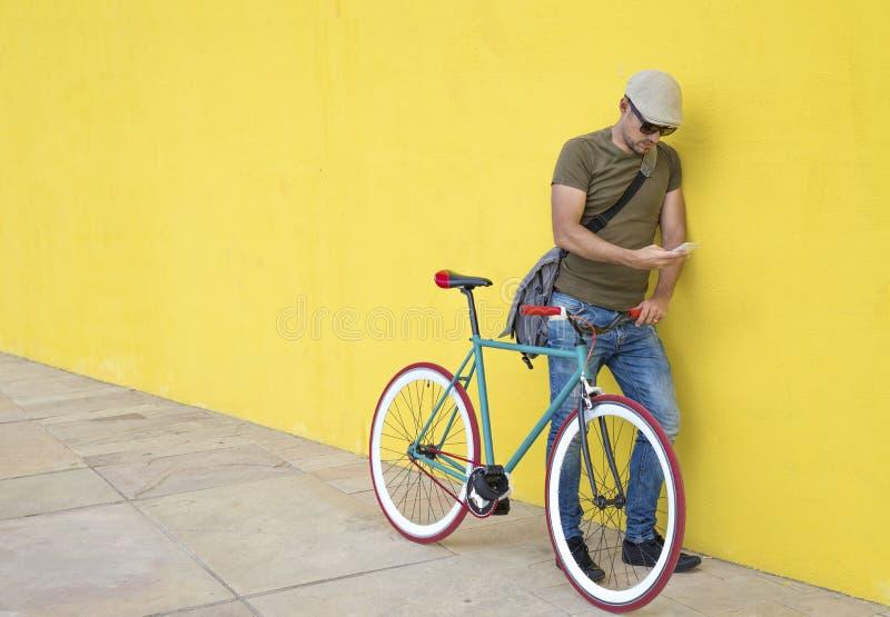 Full längd av mannen som använder den smarta telefonen, medan stå med cykeln mot den gula väggen på trottoaren i stad royaltyfri foto