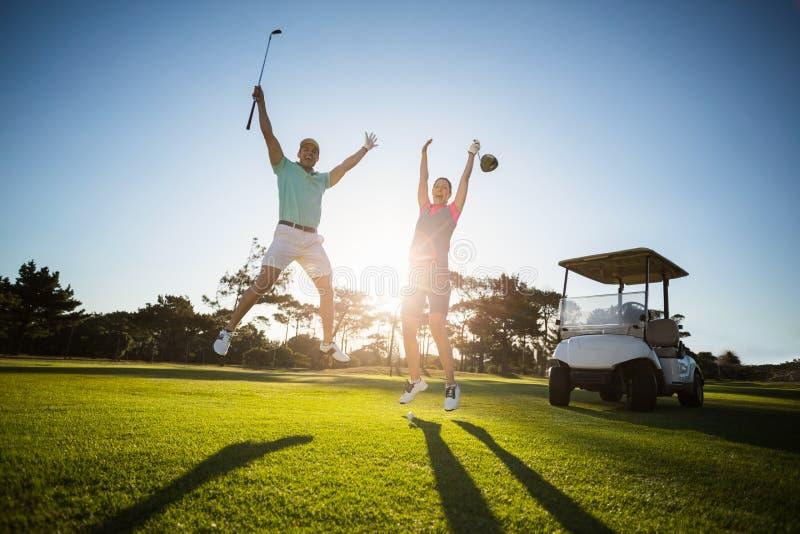 Full längd av par för golfspelare med lyftta armar arkivbilder
