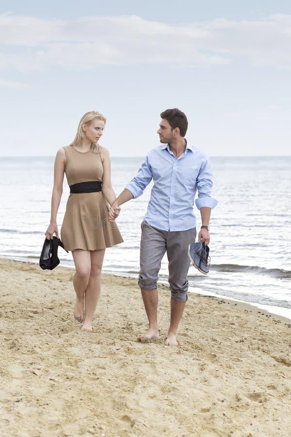Full längd av romantiska händer och att gå för barnparinnehav på stranden arkivbild
