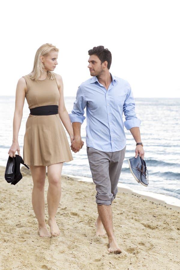 Full längd av romantiska händer och att gå för barnparinnehav på stranden royaltyfria foton