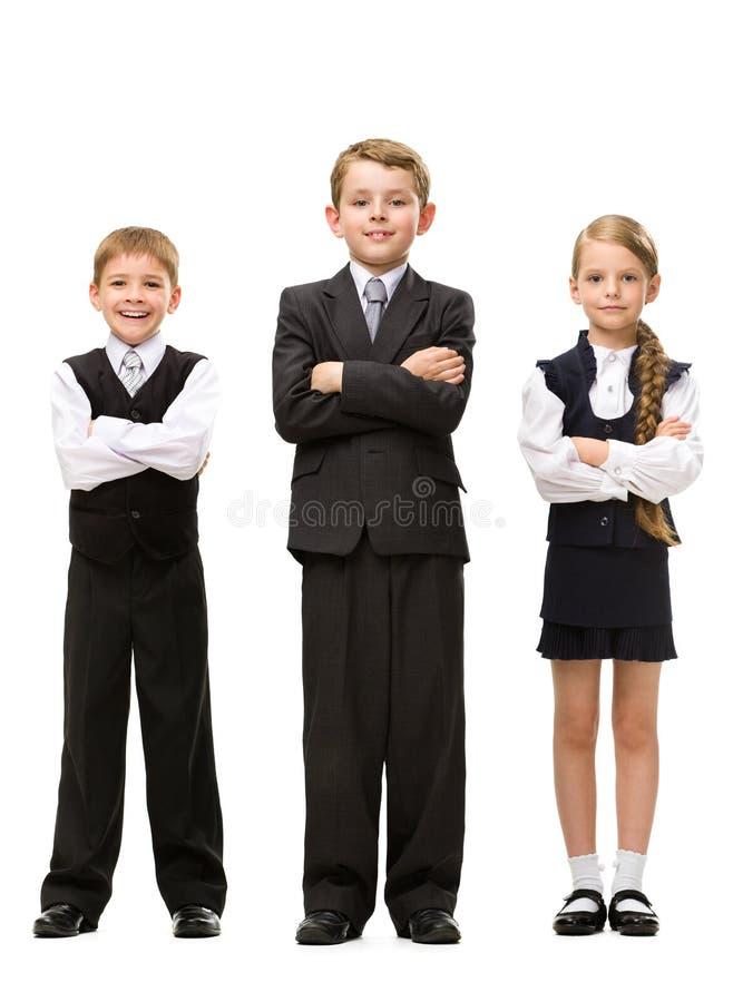 Full längd av små barn med korsade händer arkivbild