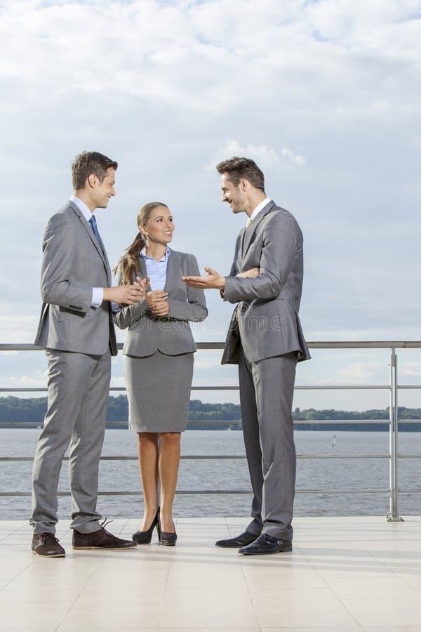 Full längd av unga businesspeople som meddelar på terrass mot himmel arkivfoto
