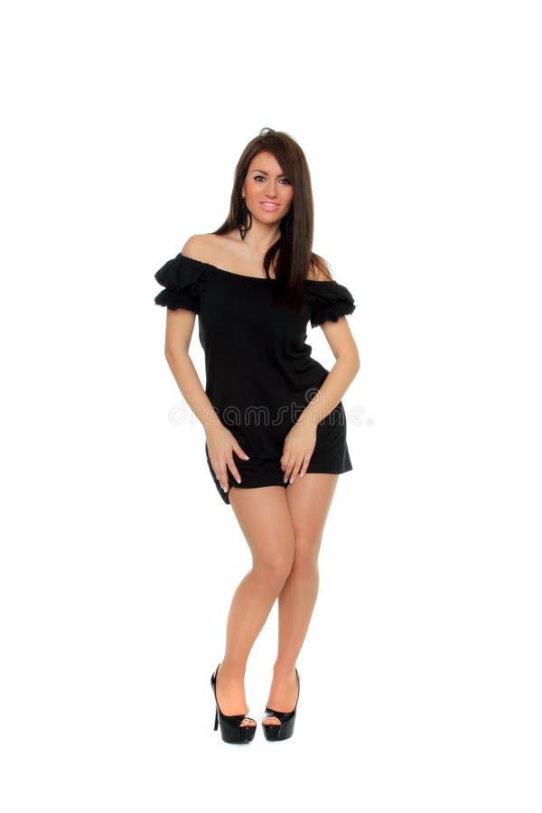 Full längd för nätt sexig flicka som poserar i en trevlig svart klänning royaltyfri foto