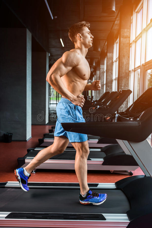 Full längd för sidosikt av den unga mannen i sportswearspring på trampkvarnen på idrottshallen royaltyfri fotografi